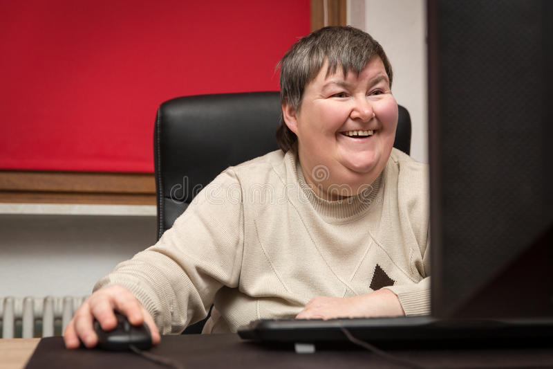 Mentalmente - mulher deficiente que senta-se no computador, na educação e no L foto de stock royalty free