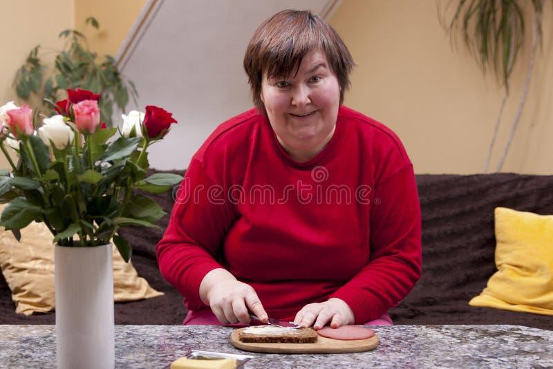 Mentalt - den rörelsehindrada kvinnan är danande upp en smörgås royaltyfri fotografi