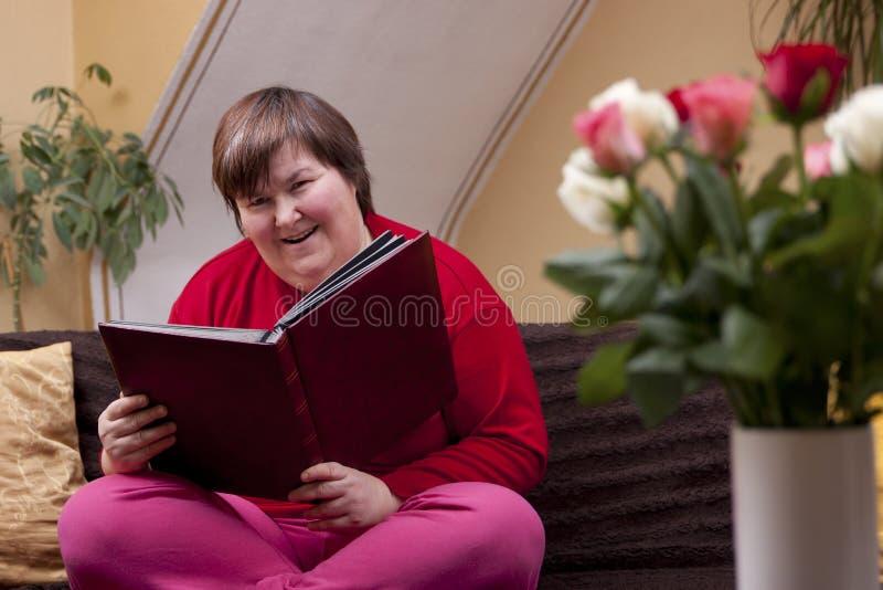 Mentalt - rörelsehindrad kvinnaläsning en boka arkivbilder