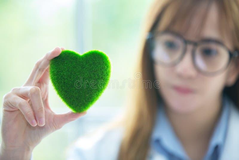 Mente do espírito do verde do whit da ciência Coração verde em sua mão no laboratório a foto de stock