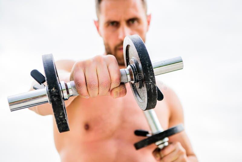 Mente sana en un cuerpo sano Hombre muscular que ejercita con pesa de gimnasia Ejercicio de la pesa de gimnasia Atrévase a ser gr foto de archivo libre de regalías