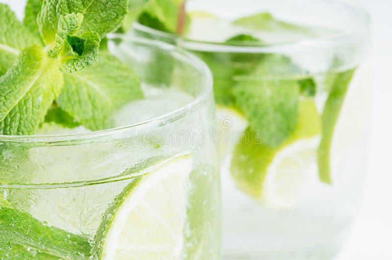 Menthe de vert de brindilles dans le mojito avec des tranches chaux, glaçons, paille, macro, texture, tache floue photos libres de droits