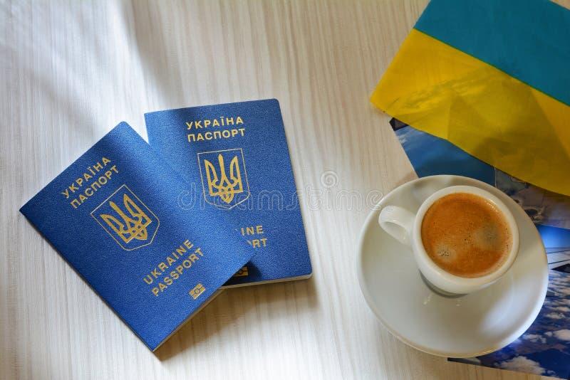 Mentira biométrica azul ucraniana nova do passaporte na tabela Passaporte biométrico ucraniano que abre uma janela a Europa fotografia de stock