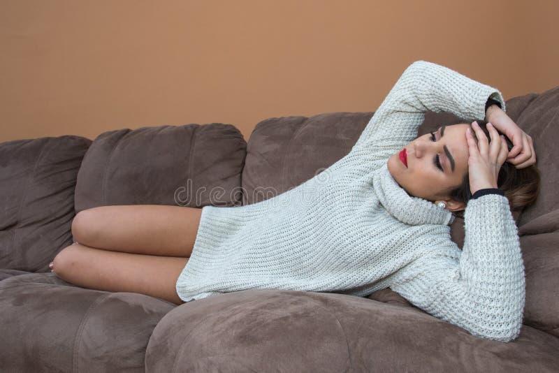 Mentira bonita de la morenita preocupante en el sofá imagen de archivo