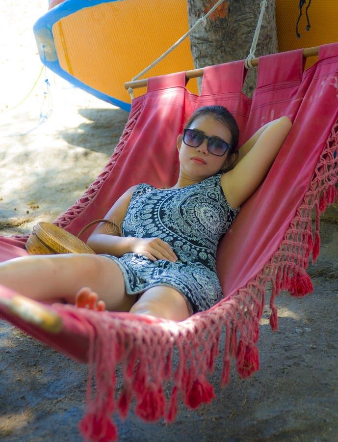 Mentira china asiática bastante feliz de la mujer de los jóvenes perezosa en la cama del sol de la hamaca de la playa relajada y  imagen de archivo