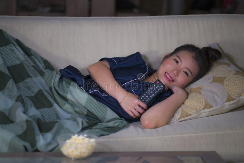 Mentira china asiática feliz y relajada hermosa joven de la sala de estar de la mujer en casa acogedora en episodio de observació imagenes de archivo