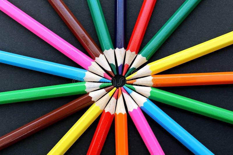 Mentira colorido dos lápis toda ao redor em um fundo preto imagens de stock royalty free