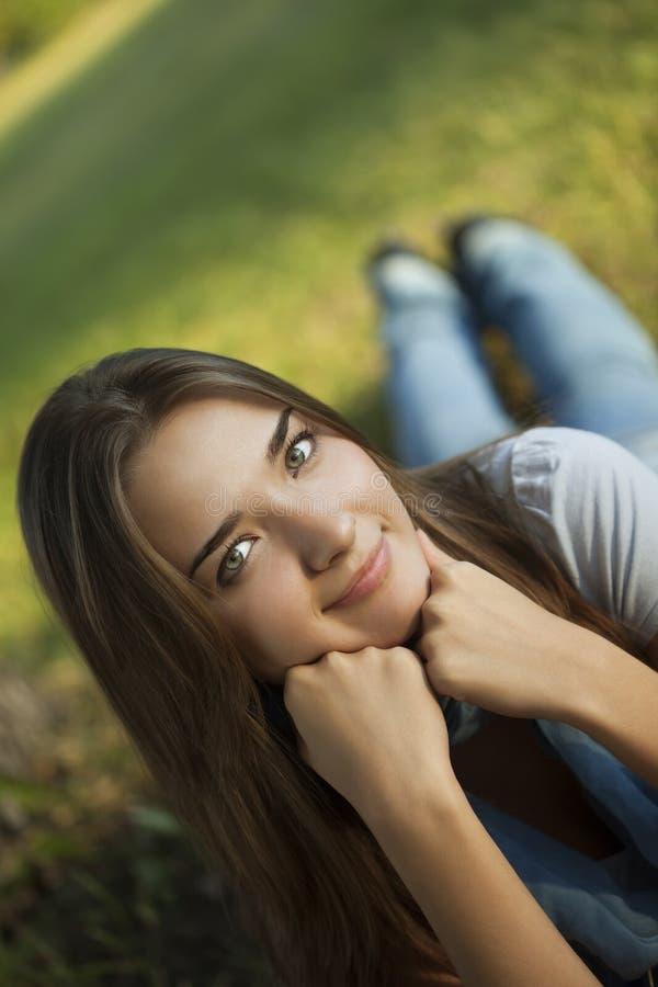Mentira da jovem mulher na grama no parque fotos de stock