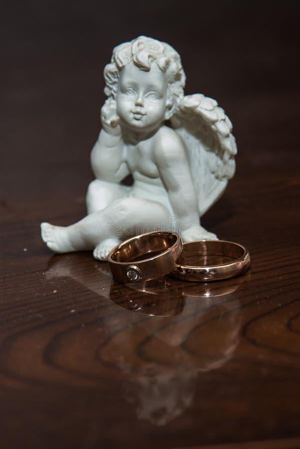 Mentira de dos anillos de bodas en la tabla Un ángel de la escultura fotografía de archivo libre de regalías