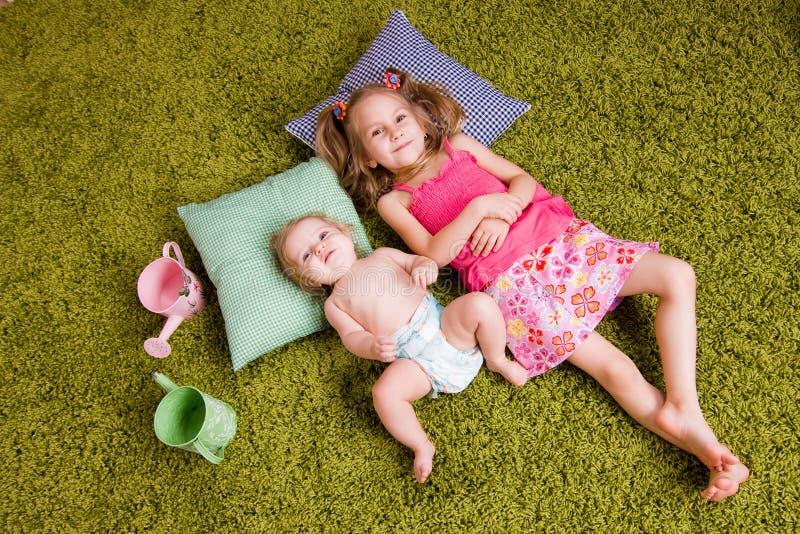Mentira de dos hermanas en la alfombra fotografía de archivo