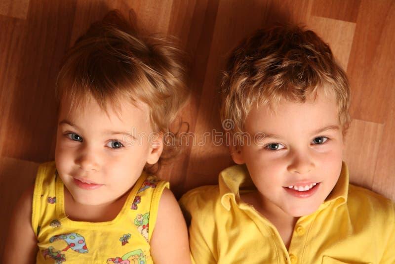 Mentira de dos niños en el suelo imagen de archivo libre de regalías