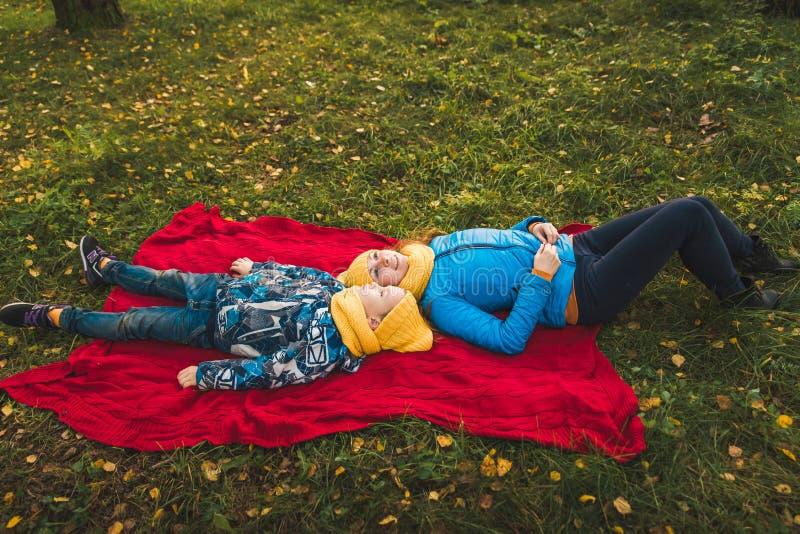 Mentira de la mamá y del hijo en una manta en la hierba fotografía de archivo libre de regalías
