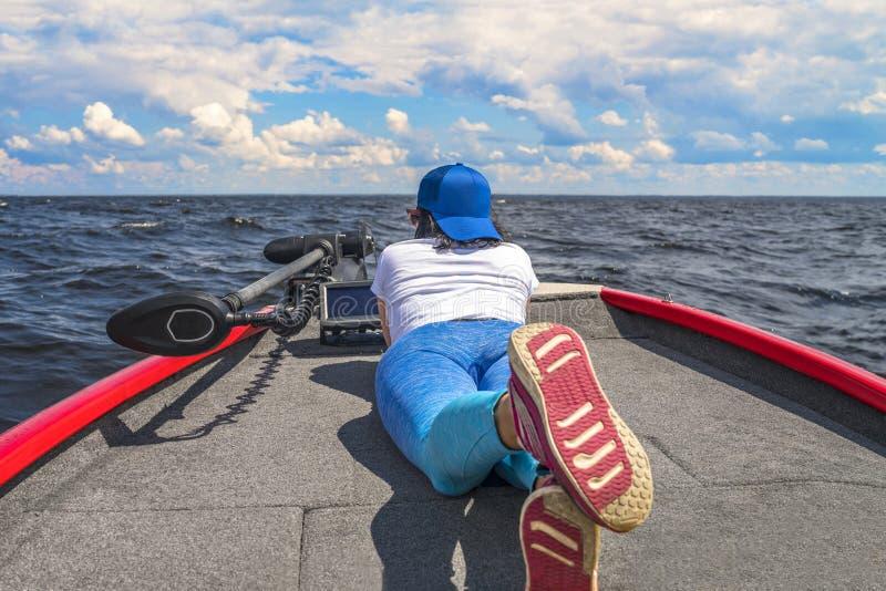 Mentira de la mujer joven en el barco de pesca con el buscador de los pescados, echolot, sonar a bordo imagen de archivo libre de regalías