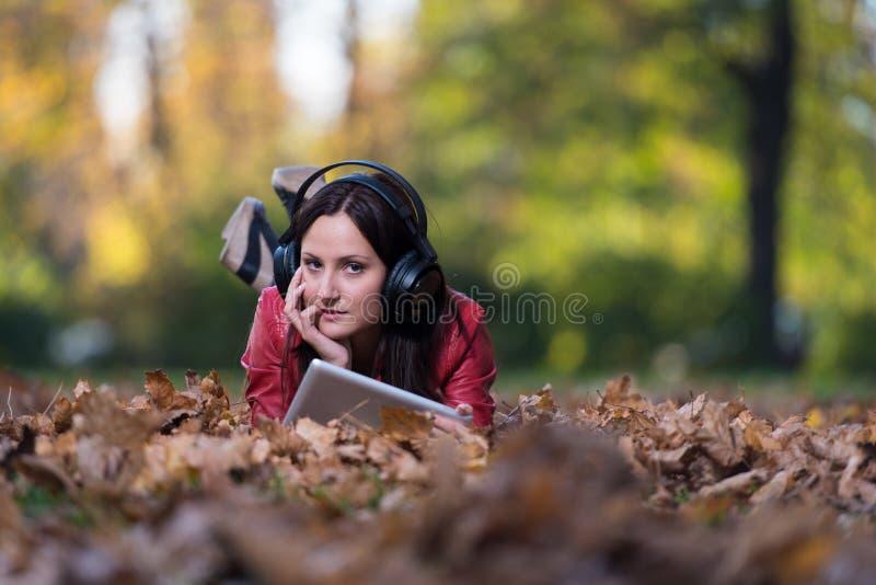 Mentira de la mujer joven exterior y el escuchar los auriculares foto de archivo libre de regalías