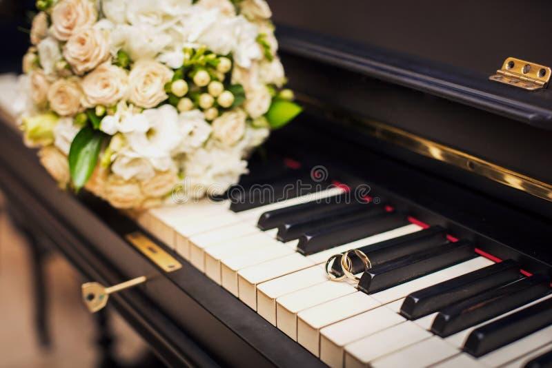 Mentira de oro de los anillos de bodas en el piano fotos de archivo