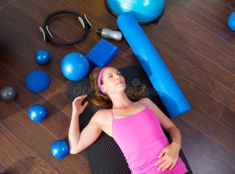Mentira de reclinación cansada mujer de los aeróbicos en la estera imagen de archivo