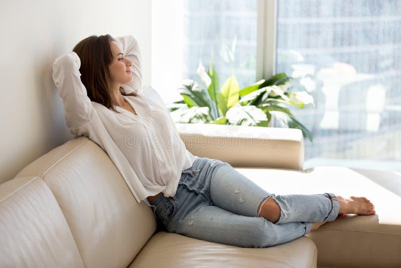 Mentira de relajación feliz de la mujer joven en el sofá acogedor imagenes de archivo