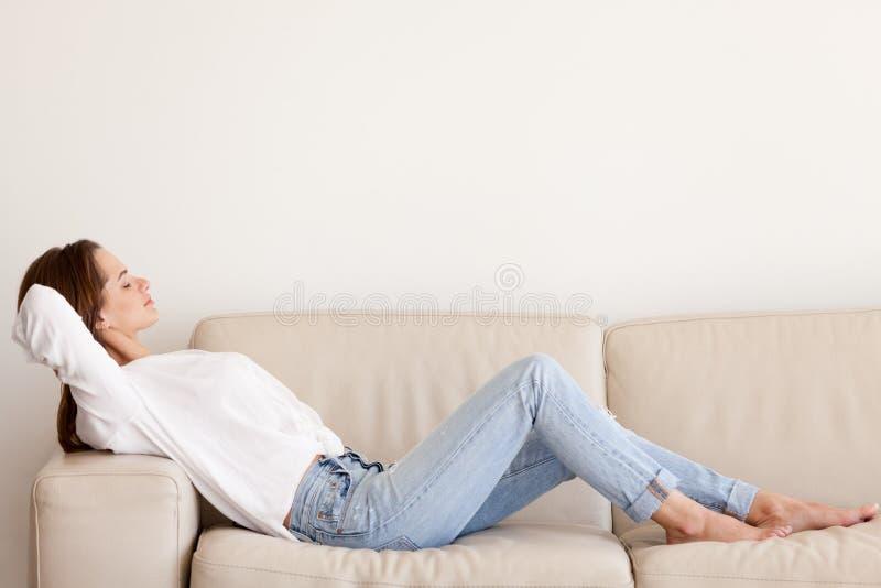 Mentira de relajación de la mujer milenaria tranquila en el sofá en el apartamento moderno imagenes de archivo