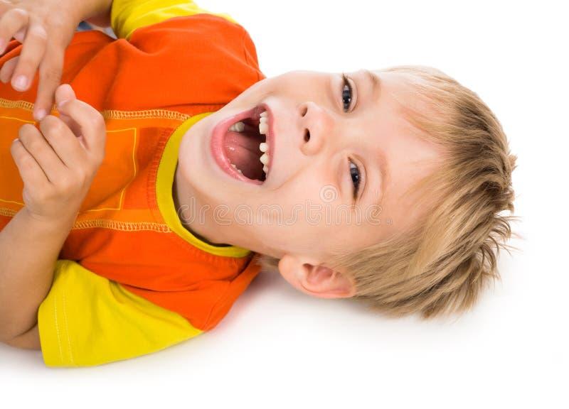 Mentira de riso do menino no fundo branco imagem de stock royalty free