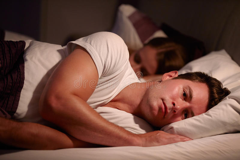 Mentira del hombre despierta en la cama que sufre con insomnio imagen de archivo