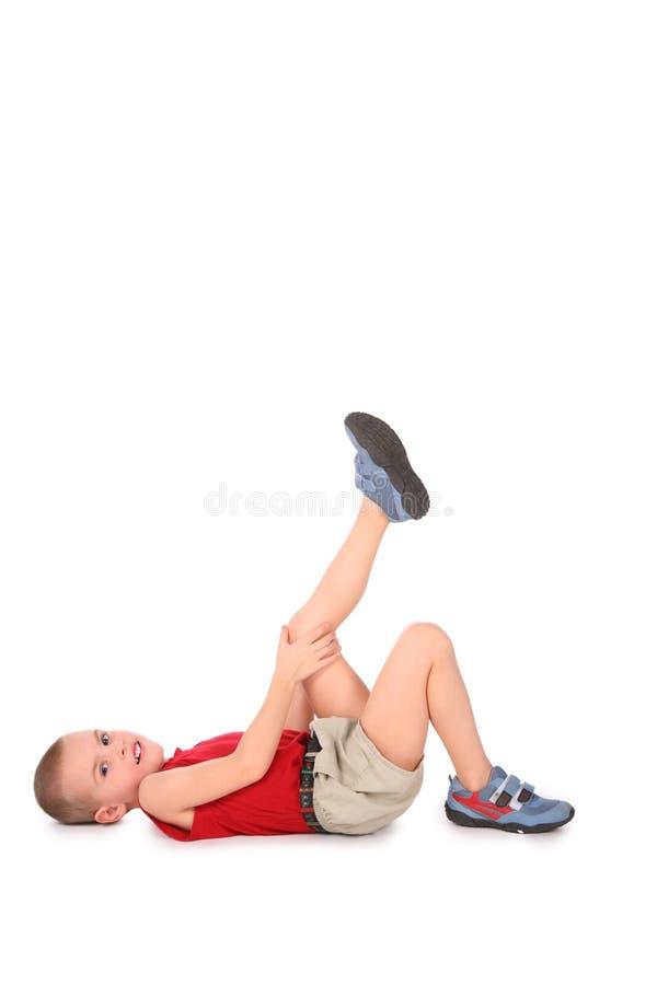 Mentira del muchacho con la pierna para arriba imágenes de archivo libres de regalías