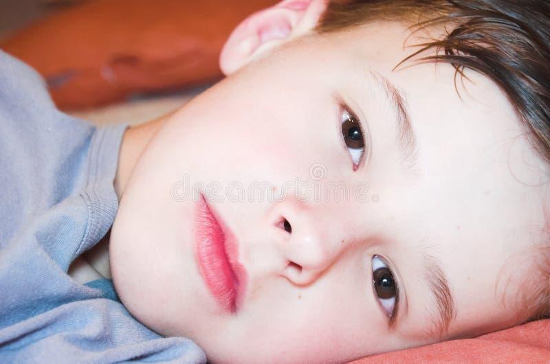 Mentira del muchacho en la cama foto de archivo
