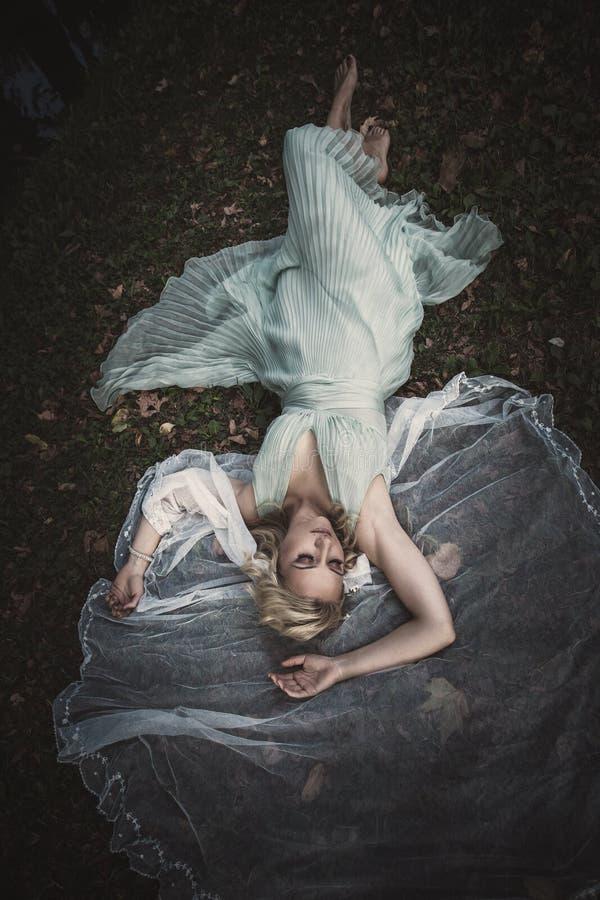 Mentira descalça da noiva em gras e em folhas com o véu em torno dela imagens de stock