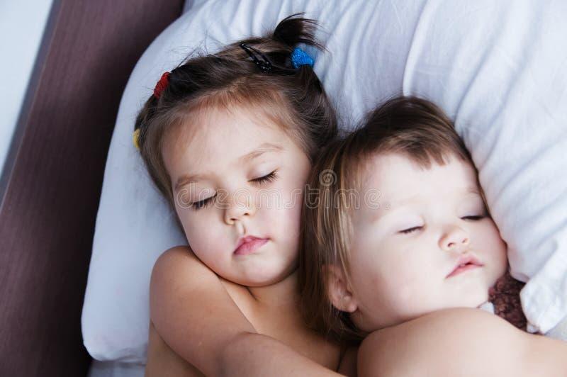 Mentira el dormir de dos niñas en cama horario del sueño del hermano en forma de vida nacional unidad de las hermanas imagen de archivo