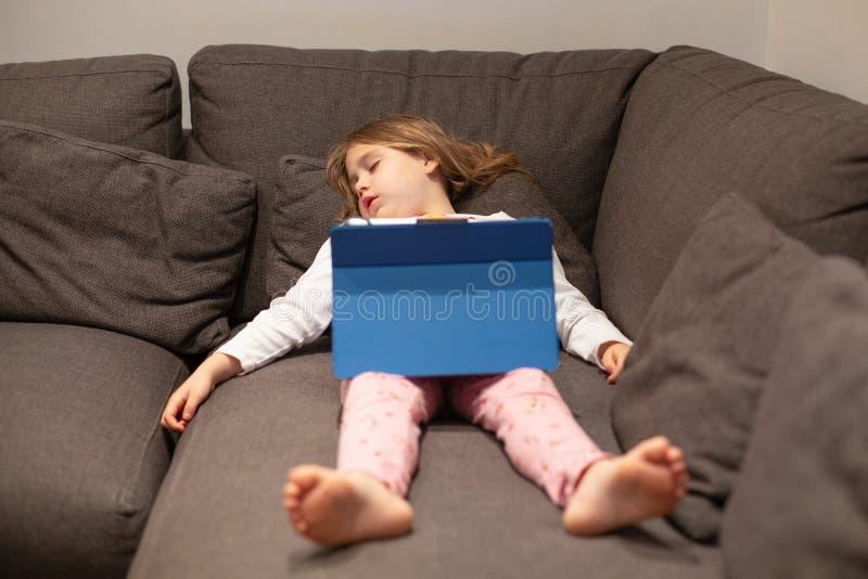 Mentira el dormir del pequeño niño en el sofá con la tableta digital fotos de archivo libres de regalías