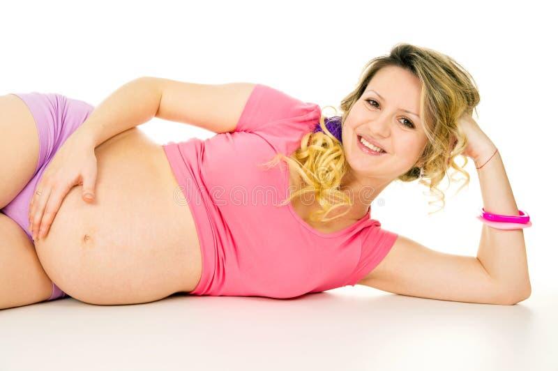 Mentira embarazada feliz de la muchacha foto de archivo
