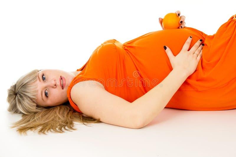 Mentira embarazada feliz y naranjas de la mujer  imágenes de archivo libres de regalías