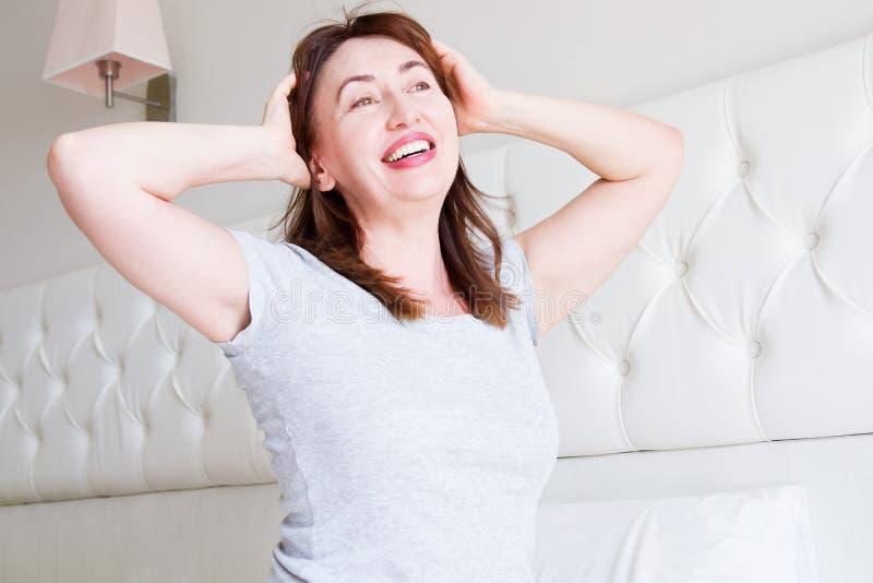Mentira envelhecida média feliz da mulher na cama Bom dia e conceito do sono Menopausa e estilo de vida saudável Foco seletivo imagem de stock royalty free