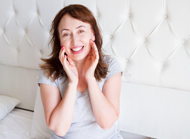 Mentira envelhecida média feliz da mulher na cama Bom dia e conceito do sono Menopausa e estilo de vida saudável Foco seletivo fotos de stock royalty free
