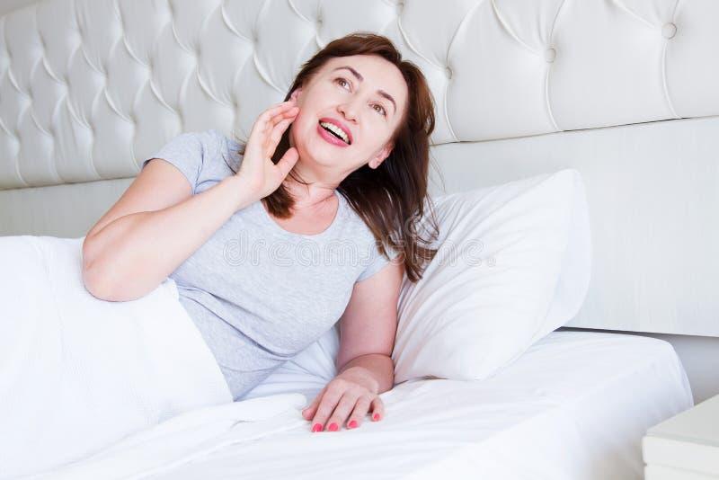 Mentira envelhecida m?dia feliz da mulher na cama Bom dia e conceito do sono Menopausa e estilo de vida saud?vel Foco seletivo foto de stock