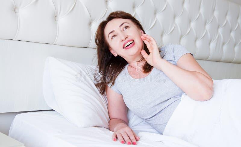 Mentira envelhecida m?dia feliz da mulher na cama Bom dia e conceito do sono Menopausa e estilo de vida saud?vel Foco seletivo ba fotos de stock royalty free