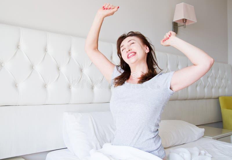 Mentira envelhecida m?dia feliz da mulher na cama Bom dia e conceito do sono Menopausa e estilo de vida saud?vel Foco seletivo ba imagem de stock