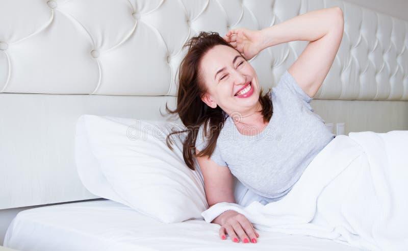 Mentira envelhecida m?dia feliz da mulher na cama Bom dia e conceito do sono Menopausa e estilo de vida saud?vel Foco seletivo ba fotos de stock