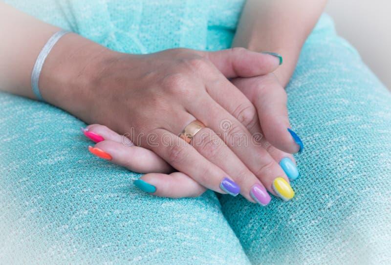 Mentira fêmea uma das mãos sobre a outro, um anel de noivado em um dedo de anel, um tratamento de mãos colorido, um vestido azul imagens de stock