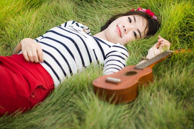 Mentira feliz asiática nova da mulher no campo verde com uquelele imagens de stock