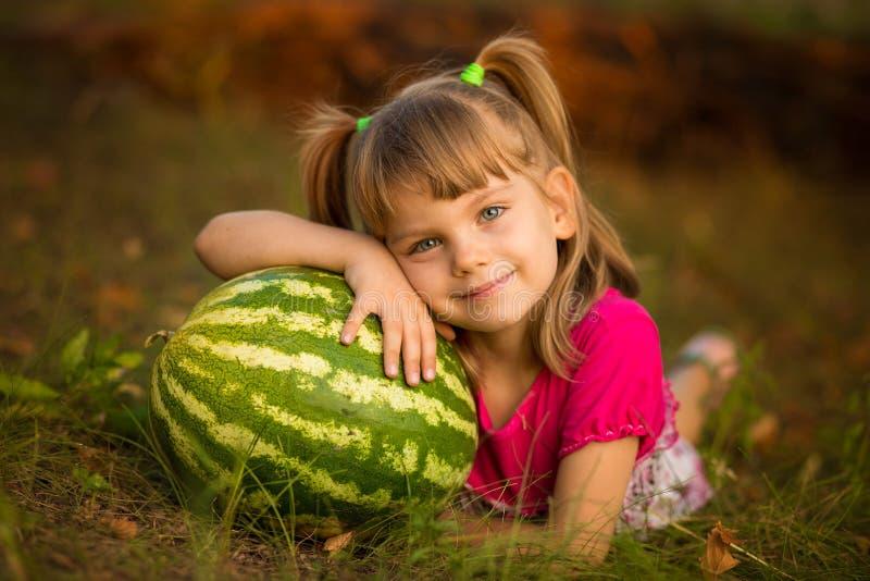 Mentira feliz da menina da criança na melancia muito grande da grama e do abraço no dia ensolarado imagens de stock