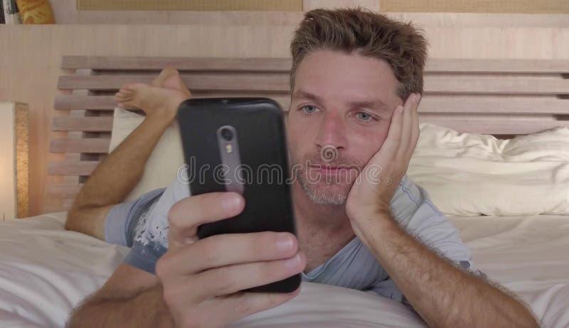 Mentira feliz 30s o 40s del hombre joven en cama en casa por la mañana usando el teléfono móvil que comprueba los medios sociales imágenes de archivo libres de regalías