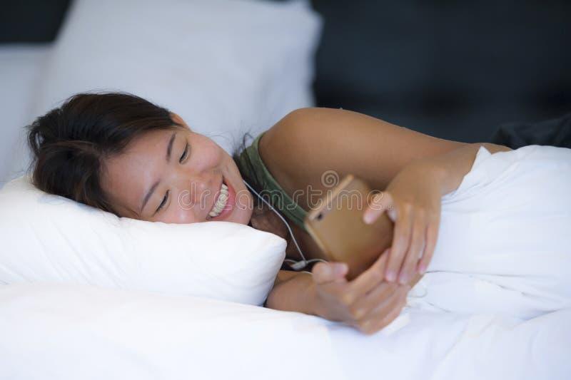 Mentira feliz sonriente joven de la mujer china asiática hermosa y relajada en dormitorio de la cama en casa usando Internet en e fotos de archivo libres de regalías