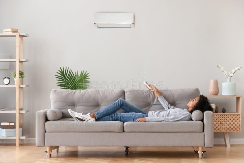 Mentira femenina africana en el acondicionador de aire del uso del sofá que respira el aire fresco fotografía de archivo