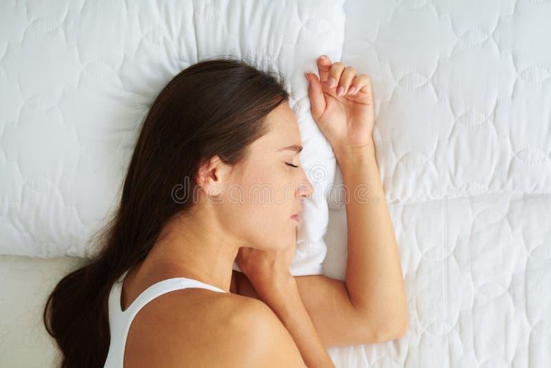 Mentira hermosa joven el dormir de la mujer en el lado en la cama imagen de archivo