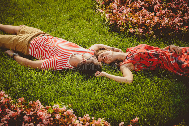 Mentira joven feliz de los pares comparativa en una hierba con las flores verano imagenes de archivo
