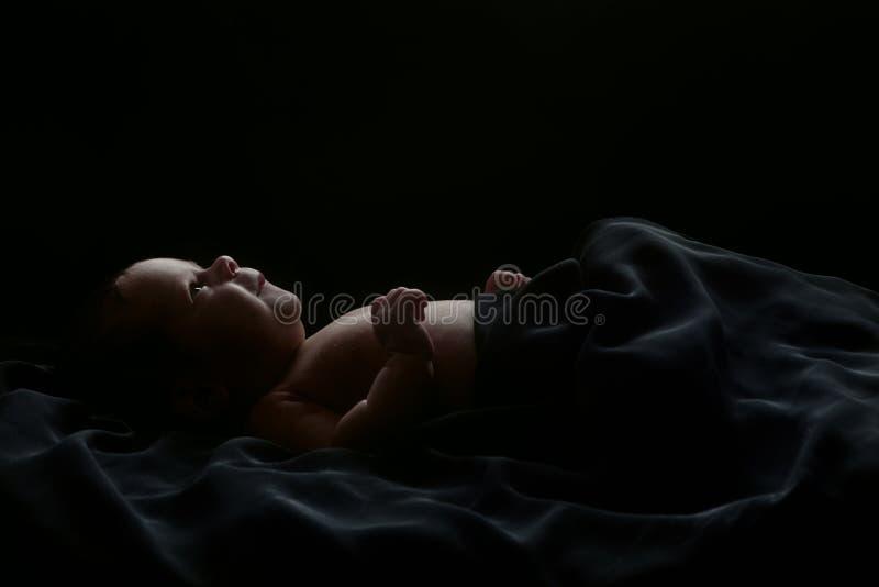 Mentira linda del bebé cubierta con la tela negra, aislada en negro fotos de archivo