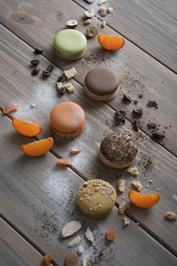 Mentira multicolora de Macarons en una tabla de madera con los diversos ingredientes, chocolate, café, mandarinas y más foto de archivo libre de regalías