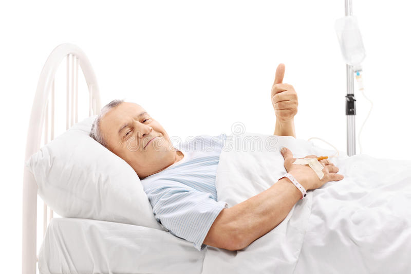 Mentira paciente mayor en cama de hospital y donante del pulgar para arriba fotografía de archivo libre de regalías