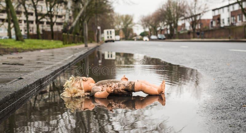 Mentira plástica de la muñeca cara arriba en un charco bajo por el borde de la carretera fotografía de archivo libre de regalías