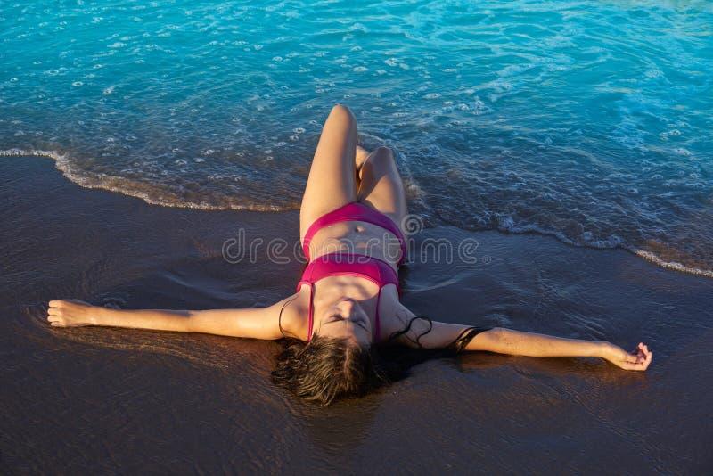 Mentira relajada de la muchacha del bikini en la arena de la playa foto de archivo